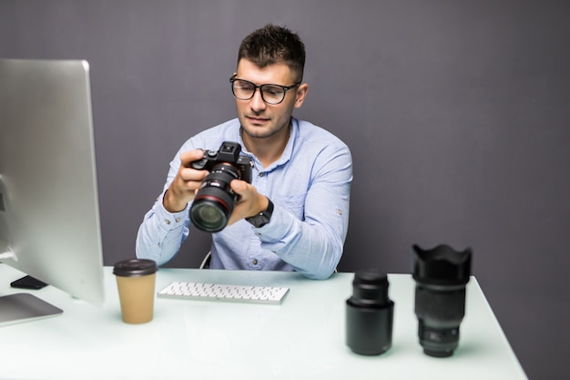 Jonge man met digitale camera en lachend zittend op zijn werkplek