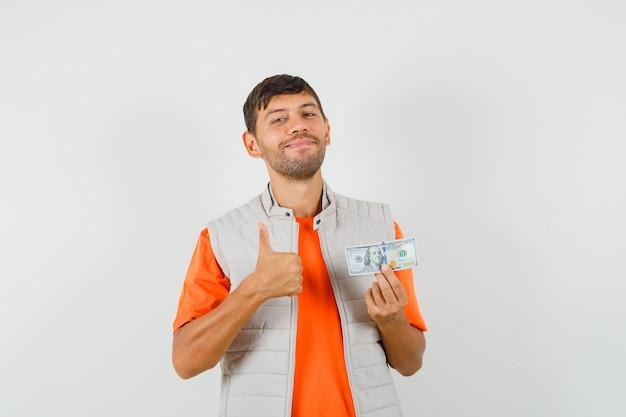 Jonge man met dollarbiljet, duim opdagen in t-shirt, jasje en op zoek vrolijk, vooraanzicht.