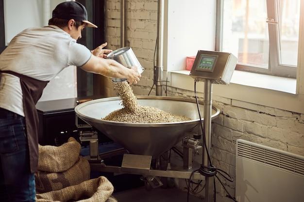 Jonge man met dop die groene koffiebonen in een metalen trechter giet terwijl hij elektronische weegschalen gebruikt