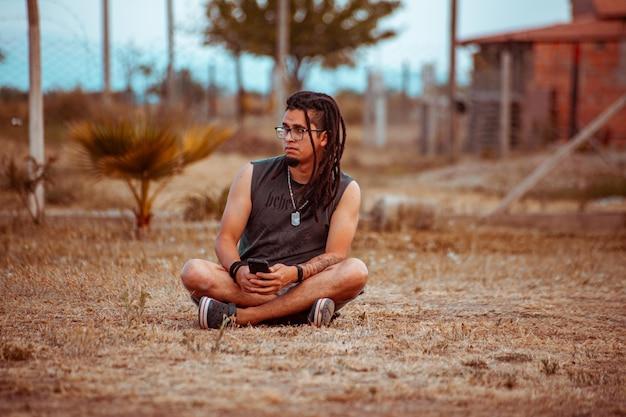 Jonge man met dreadlocks zittend op de vloer