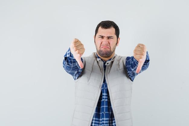 Jonge man met duim naar beneden in shirt, mouwloos jasje en op zoek naar dissatified. vooraanzicht.