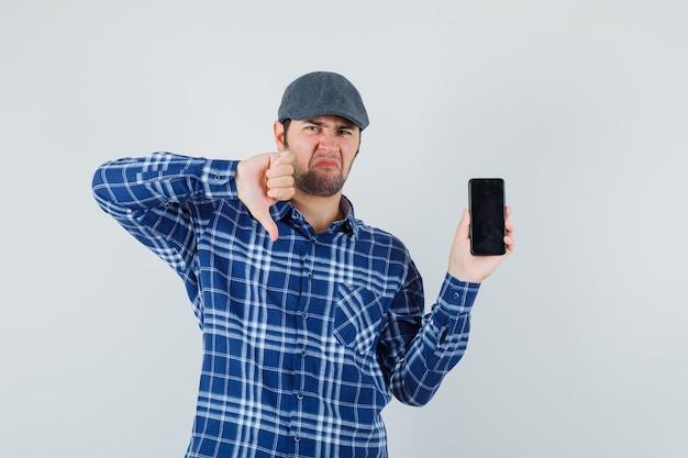 Jonge man met duim naar beneden, mobiele telefoon in shirt, pet vast te houden en ontevreden op zoek. vooraanzicht.