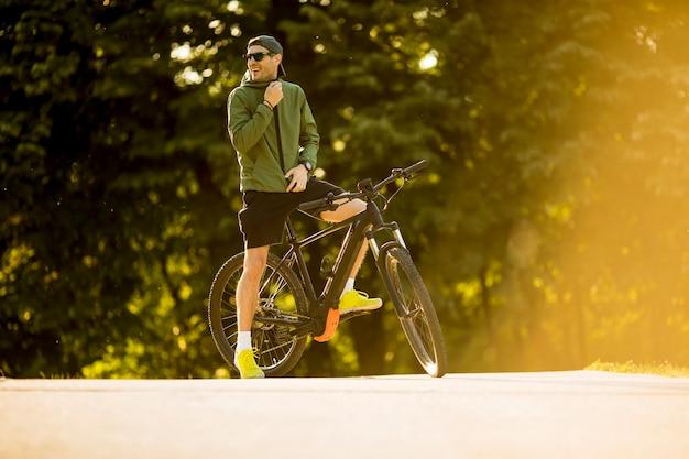 Jonge man met ebike, mountainbike met elektrische batterij in het park