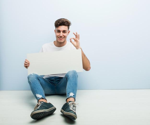 Jonge man met een aanplakbiljet zittend op zijn huis vloer vrolijk en vol vertrouwen weergegeven: ok gebaar.