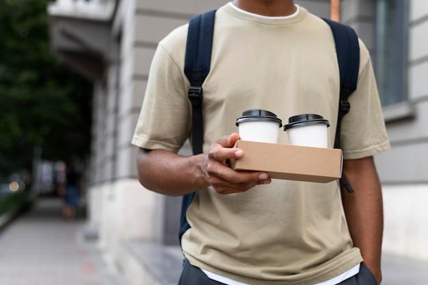 Jonge man met een afhaalkoffie