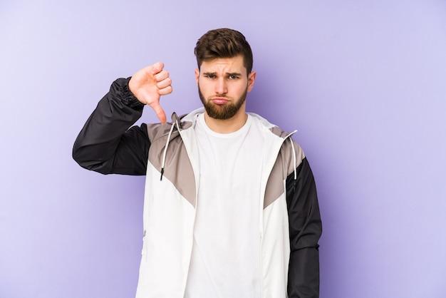 Jonge man met een afkeer gebaar, duimen naar beneden. meningsverschil concept.