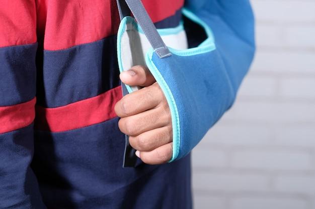 Jonge man met een arm brace voor gebroken hand.