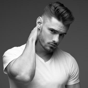 Jonge man met een baard. een man in een t-shirt. mannelijk portret op een grijze achtergrond. stijlvolle man. zwart-wit foto. sport man. mannelijk geschiktheidsmodel. studio portret