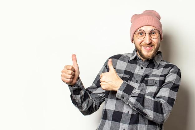 Jonge man met een baard in een hoed, een geruit hemd maakt een gebaar duim omhoog op een afgelegen wit. het gebaar is in orde, oké, geverifieerd