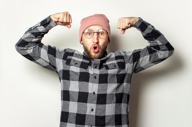Jonge man met een baard in een hoed, een geruite overhemd toont biceps met een verbaasd gezicht op een afgelegen wit. gebaar van macht