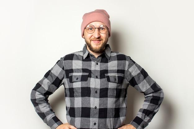 Jonge man met een baard in een hoed, geruite hemd en een bril houdt zijn handen in de taille en glimlacht op een afgelegen wit.