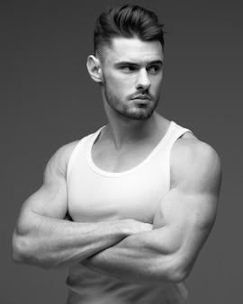 Jonge man met een baard in een t-shirt. mannelijk portret op een grijze achtergrond. stijlvolle man. zwart-wit foto. sport man. fitness model. studio portret. stijlvolle mannelijke portret op een grijze achtergrond.