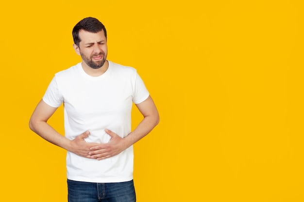 Jonge man met een baard in een wit t-shirt met een hand op zijn buik vanwege indigestie, misselijkheid.