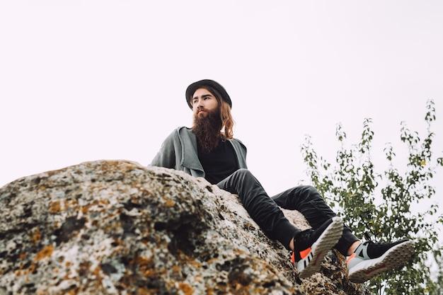Jonge man met een baard zit op een rots en kijkt vanaf een hoogte naar de natuur.