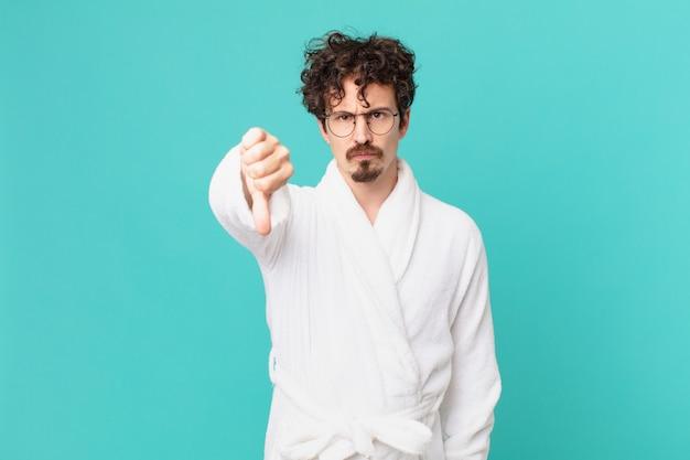 Jonge man met een badjas die zich boos voelt en zijn duimen naar beneden laat zien