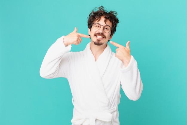 Jonge man met een badjas glimlachend vol vertrouwen wijzend naar zijn eigen brede glimlach
