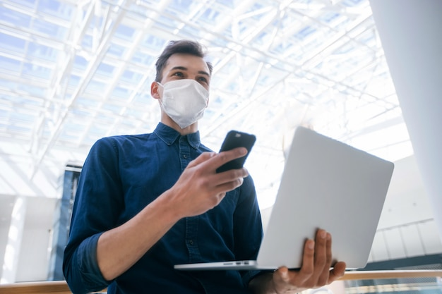 Jonge man met een beschermend masker kiest een contact in zijn smartphone. pandemie in de stad