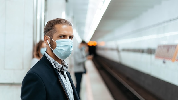 Jonge man met een beschermend masker staande op een metrostation