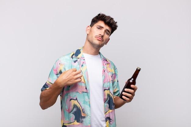 Jonge man met een biertje die er arrogant, succesvol, positief en trots uitziet, wijzend naar zichzelf