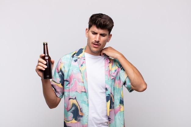 Jonge man met een biertje voelt zich gestrest, angstig, moe en gefrustreerd, trekt de hals van het shirt aan en kijkt gefrustreerd door het probleem