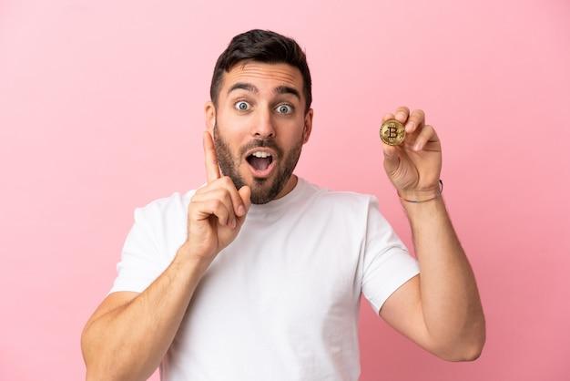 Jonge man met een bitcoin geïsoleerd op een roze achtergrond met de bedoeling de oplossing te realiseren terwijl hij een vinger optilt