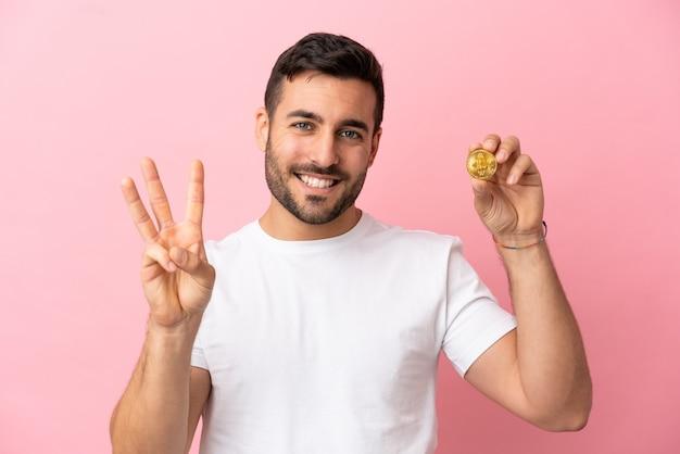 Jonge man met een bitcoin geïsoleerd op roze achtergrond gelukkig en drie tellen met vingers