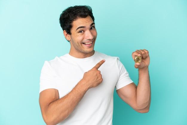 Jonge man met een bitcoin over geïsoleerde blauwe achtergrond die naar achteren wijst