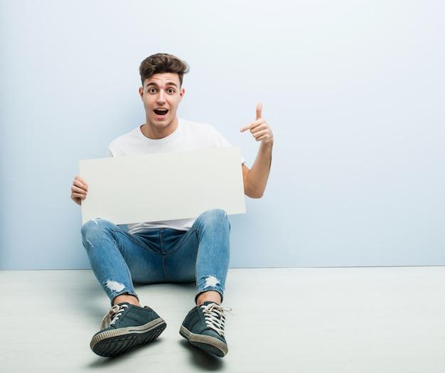 Jonge man met een bordje zittend op zijn huis vloer glimlachend opgewekt wijzen met wijsvinger weg.