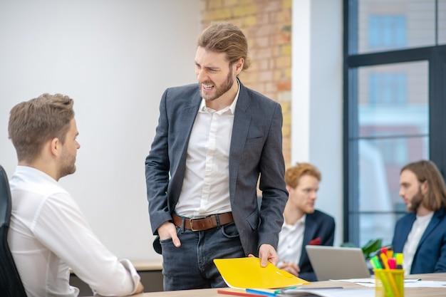 Jonge man met een boze grimas met documenten staan in de buurt van werknemer aan tafel zitten