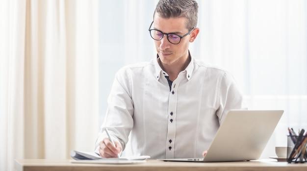 Jonge man met een bril die notities opschrijft in een notitieblok met een notitieboekje op het bureau voor hem.