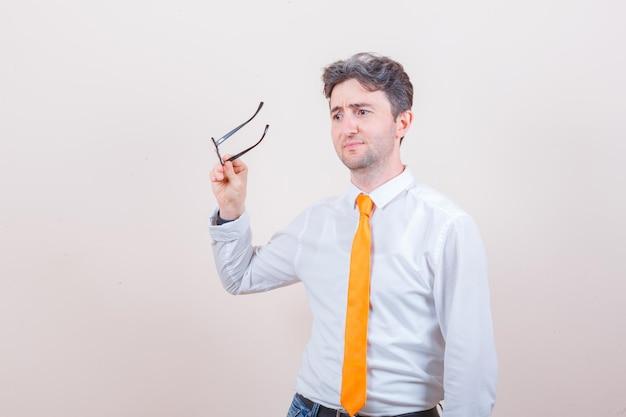 Jonge man met een bril in shirt, spijkerbroek en op zoek naar ontevredenheid