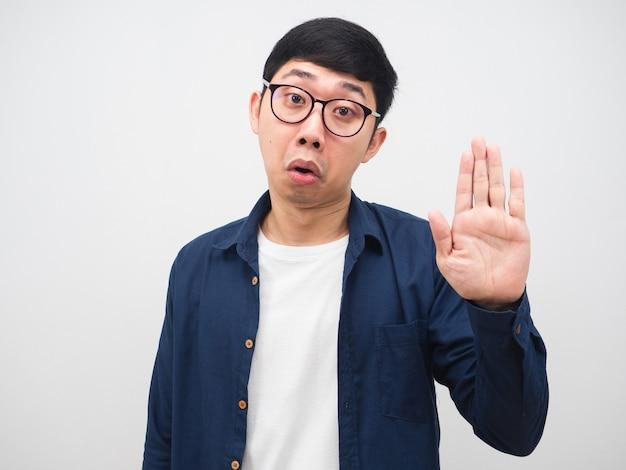 Jonge man met een bril zegt nee en laat zijn hand zien om de witte achtergrond te stoppen