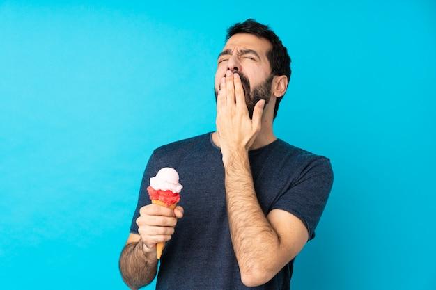 Jonge man met een cornet-ijs dat en wijd open mond geeuwt met hand