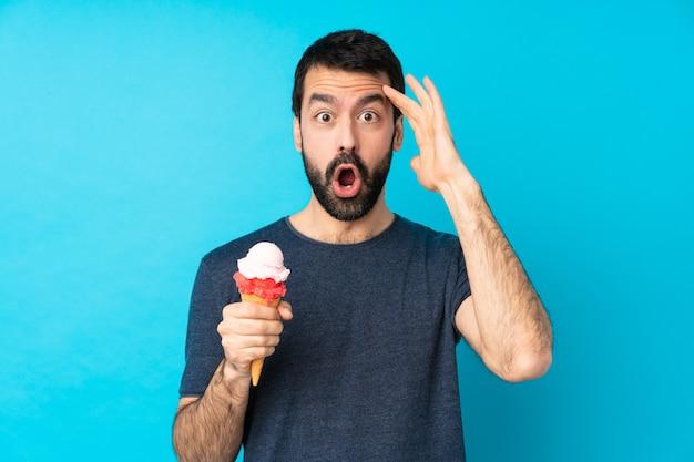 Jonge man met een cornet-ijs heeft zich net iets gerealiseerd en heeft de oplossing voor ogen