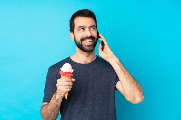 Jonge man met een cornet ijs over blauw houden van een gesprek met de mobiele telefoon
