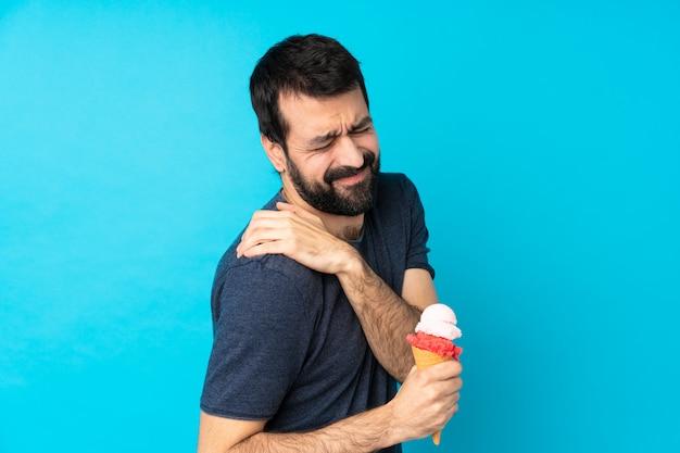 Jonge man met een cornet ijs over blauw lijden aan pijn in de schouder voor het hebben gedaan van een inspanning
