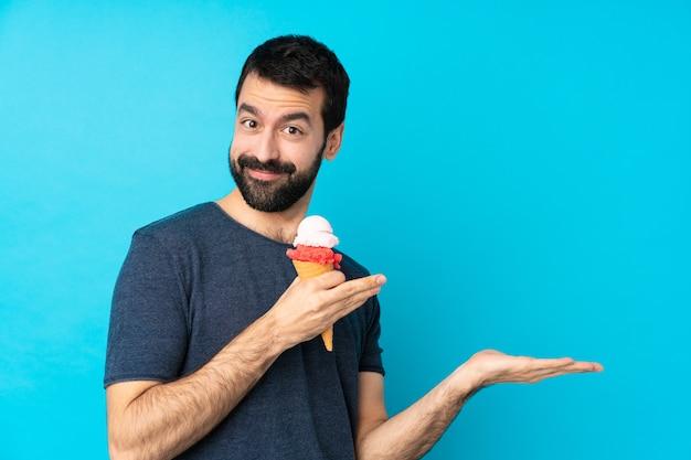 Jonge man met een cornet-ijs over geïsoleerde blauwe muur die handen naar de zijkant uitstrekt voor het uitnodigen om te komen