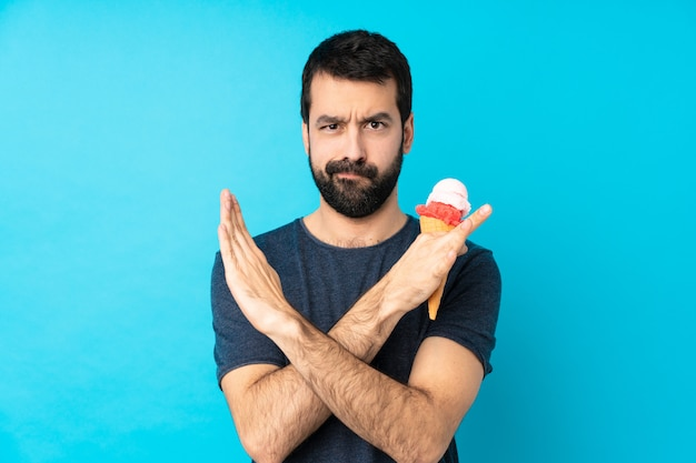 Jonge man met een cornet ijs over geïsoleerde blauwe muur geen gebaar maken