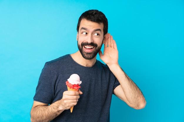 Jonge man met een cornet ijs over geïsoleerde blauwe muur luisteren naar iets door de hand op het oor te zetten