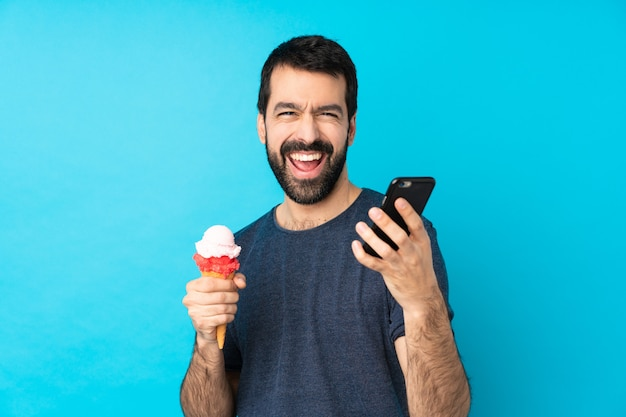 Jonge man met een cornet-ijs over geïsoleerde blauwe muur met telefoon in overwinningspositie