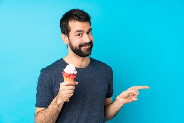 Jonge man met een cornet ijs over geïsoleerde blauwe muur wijzende vinger naar de kant