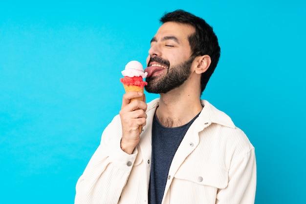 Jonge man met een cornet-ijs over geïsoleerde blauwe muur