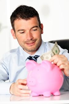 Jonge man met een dollar en een spaarvarken