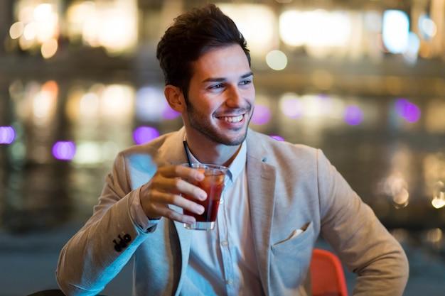 Jonge man met een drankje in een nachtclub buiten