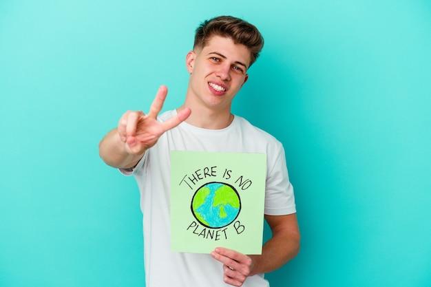 Jonge man met een er is geen bordje planeet b geïsoleerd op blauwe muur