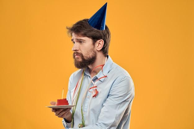 Jonge man met een feestelijke taart met plakjes viert een verjaardag in een dop