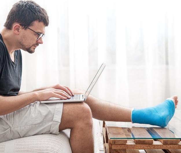 Jonge man met een gebroken been in blauwe spalk voor behandeling van blessure en enkelverstuiking gebruikt thuis een laptop.