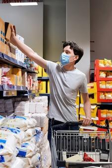Jonge man met een gezichtsmasker kijken naar snacks in een supermarkt