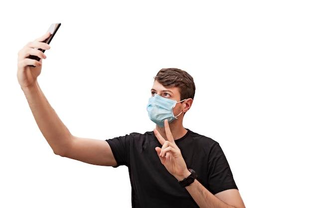 Jonge man met een gezichtsmasker met zijn mobiele telefoon om een selfie te maken