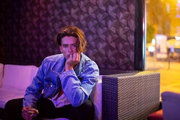 Jonge man met een glas rum in een bar met een chillout-sfeer.